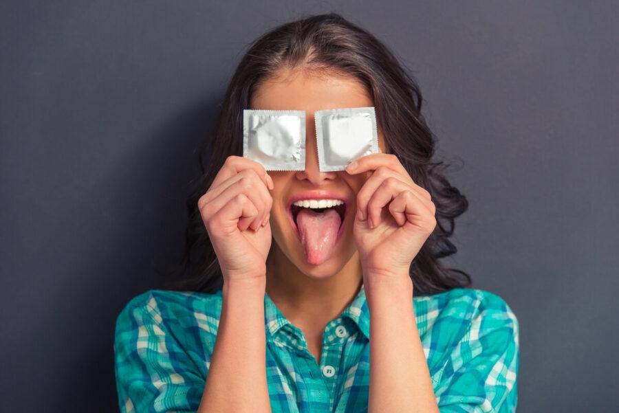 девушка держит 2 презерватива