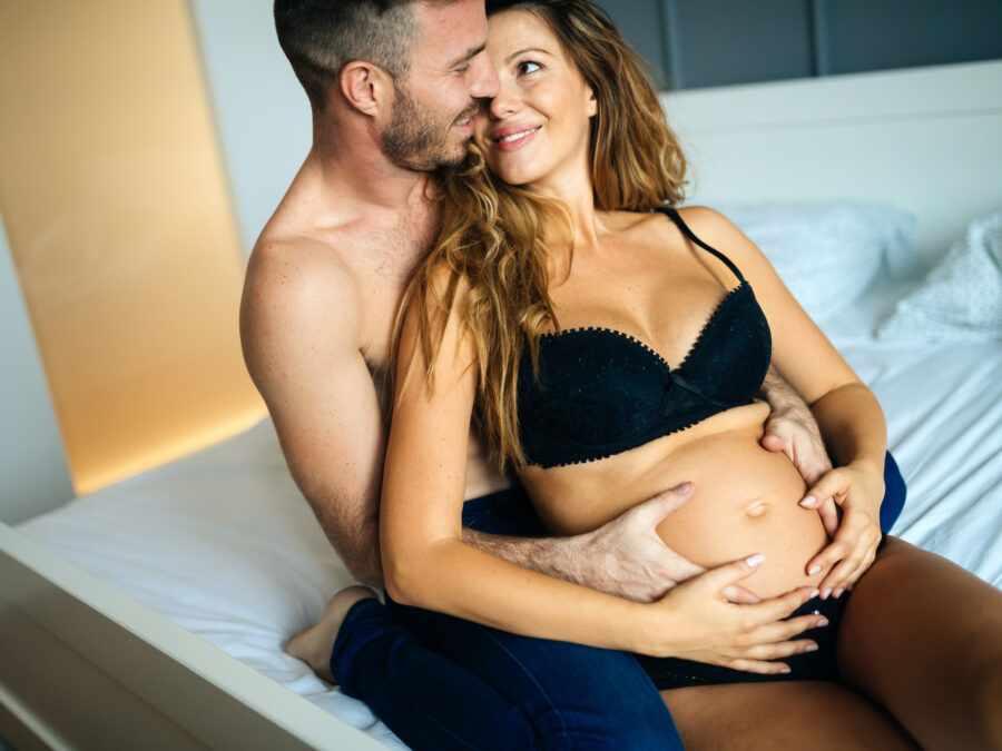 мужчина держит животик женщины