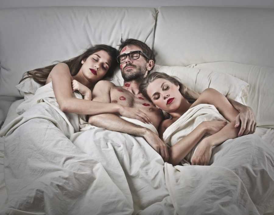 Две девушки с парнем в постели