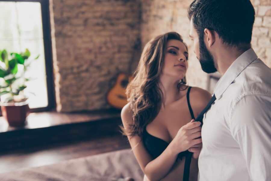 девушка тянет мужчину в кровать