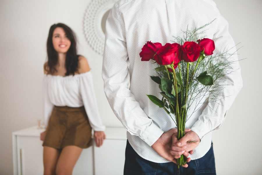 Парень с цветами перед девушкой