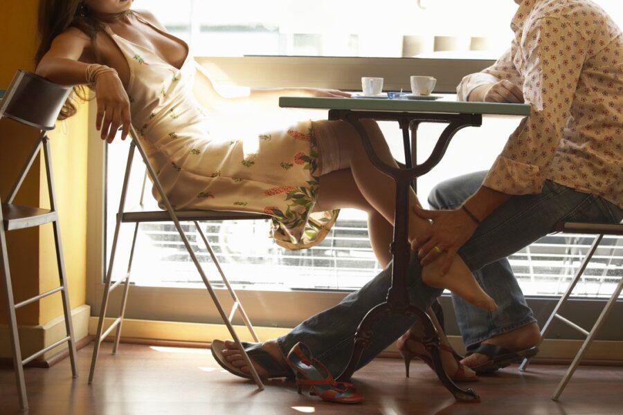 парень гладит девушку под столом