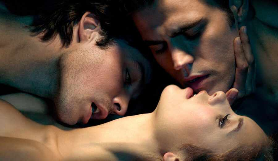 два парня целуют девушку