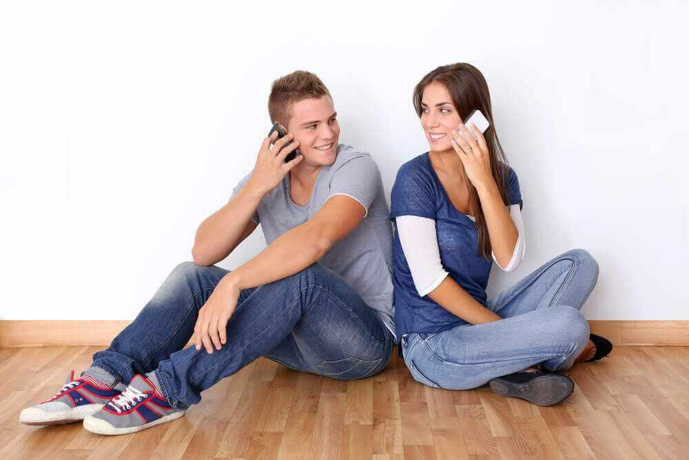 Парень с девушкой разговаривают оп телефону